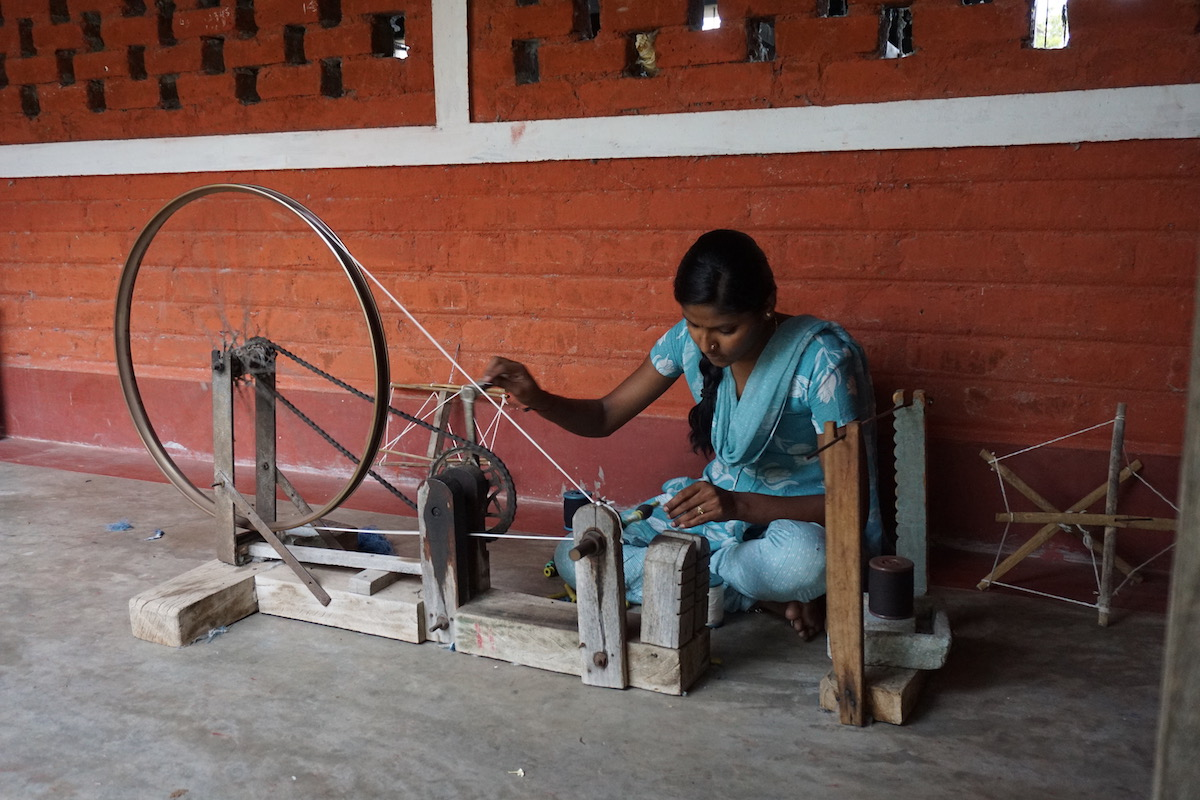 Handspinning of cotton using a recycled bicycle wheel at the Janapada Seva Trust.